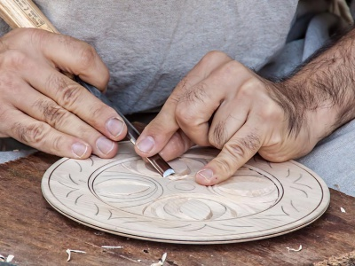 A craftsman handcarving a decorative plate
