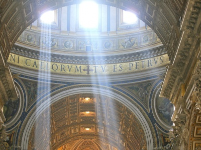 Rays of sunlight filter through windows in the dome of St. Peter's Basilica