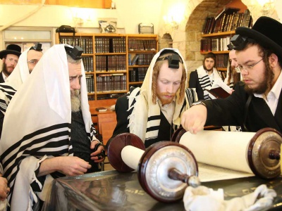Jewish scholars gather around Torah scrolls during morning prayers